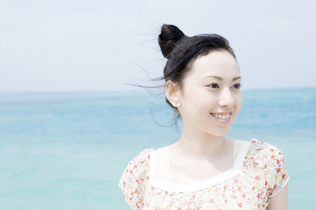 Woman showing smiling face with their back against blue sea