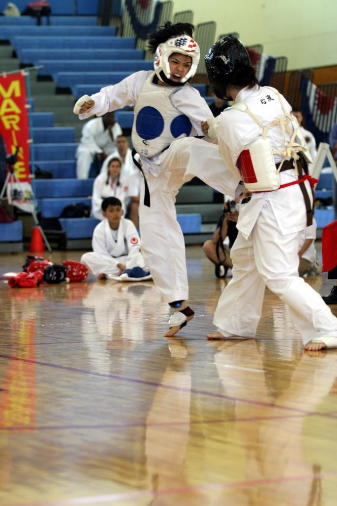 Release0204-2004-05 MARINE CORPS AIR STATION FUTENMA, Okinawa, Japan - Suan Sharon shouts as she delivers a kick to Jennie Porter during the final kumite, or sparring match, of the 16 to 17-year old female category of the Open Karate Tournament. Sharon went on to win the match, and best overall female performance. (Released) Official photo by Lance Cpl. Chris Korhonen